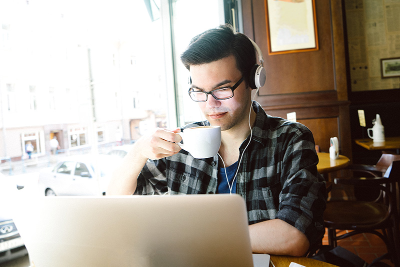 Virtual Learning - Guy at laptop in coffee shop